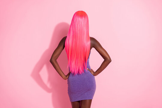 Photo portrait back view of african american woman with pink wig isolated on pastel pink colored background