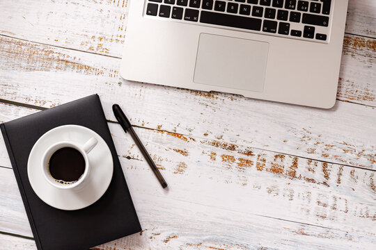 Flat lay on washed wooden background with cup of cofee, laptop and a cel phone