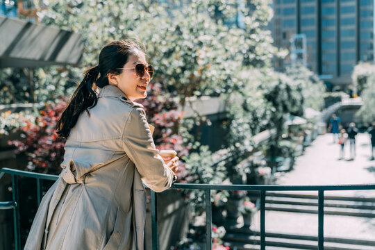 back view elegant young asian japanese woman standing outdoor modern office building in city and holding take away coffee. smiling office lady employee leaning on railing looking side on sunny day.