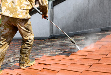 Obraz Professional in uniform using high pressure machine to clean rooftop from dirt and lichen. Before and after situation. Clean and dirty roof tiles. - fototapety do salonu