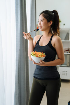 side view slim young woman eating salad standing by window with sunshine. asian girl in fitness clothes having healthy breakfast at home. Fit female having vegan food meal after workout in apartment.