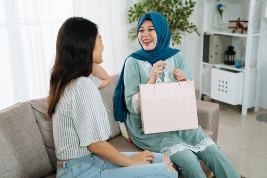 Attractive pregnant muslim woman at home living room with female friend celebrating baby shower. young girl sending gift in shopping bag for unborn baby in big abdomen. cheerful mom holding present.