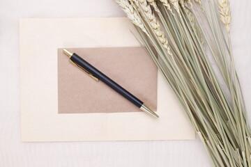 Obraz Czarno złoty długopis na beżowej kartce i suszone kwiaty  - fototapety do salonu