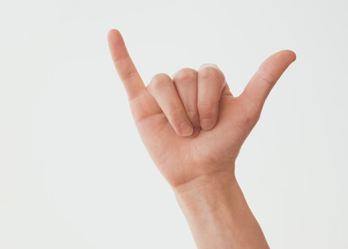 Woman hand in shaka or calling gesture on a white isolated background.