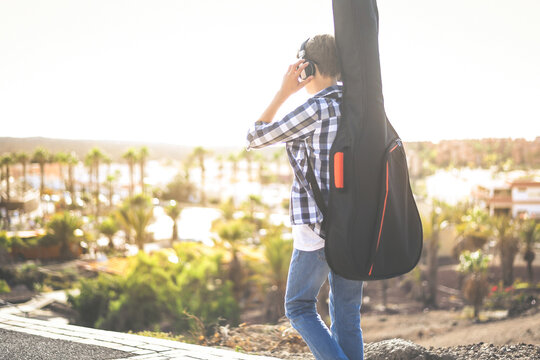 Trendy young caucasian boy walking outdoor with guitar on his shoulders like a backpack. Teen going to school listening music, exotic panorama in background. Freedom, education, fun and youth concept.