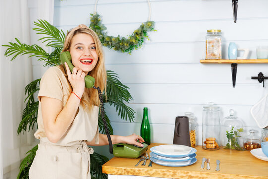 Young cheerful pretty woman talking on the old vintage phone in the kitchen