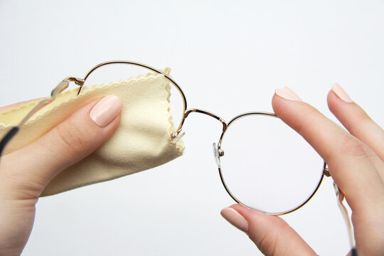 The girl manually cleans the lenses of her reading glasses on a light background. A soft cloth for wiping glasses and optics from dirt and dust. The concept of cleaning and caring for glasses.