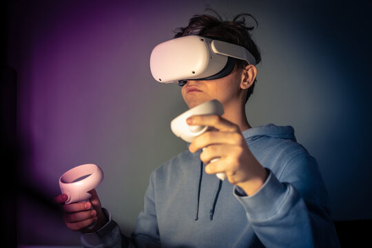 Teenager playing with virtual reality device. Cyberpunk futuristic mood, immersive experience with video game and VR 3D viewer technology. People using next-generation electronic devices. Tech concept