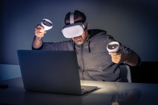 Man playing with virtual reality device. Cyberpunk futuristic mood, immersive experience with video game and VR 3D viewer technology. People using next-generation electronic devices. Tech concept