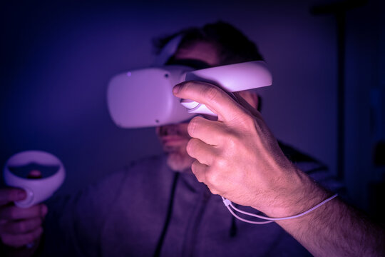 Closeup of young hands playing with virtual reality device. Cyberpunk futuristic mood, immersive experience with video game and VR 3D viewer technology. People using next-generation electronic devices