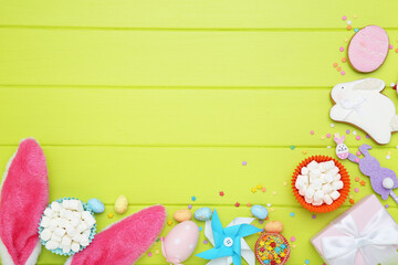 Easter concept. Gingerbread cookies with eggs, rabbit ears and sprinkles on green wooden table