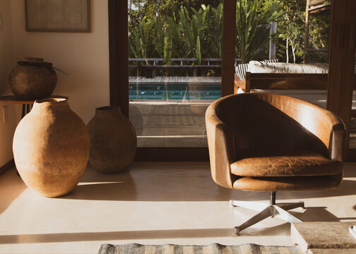 Modern luxury summer holiday or vacation beach house living room interior with rustic ceramic clay vases and armchair on the foreground and view of the swimming pool through the glass door.
