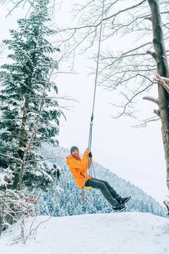 A young man in an orange softshell jacket laughing while he swinging on a swing between forest trees with picturesque snowy mountain view. Wintertime vacation concept image.