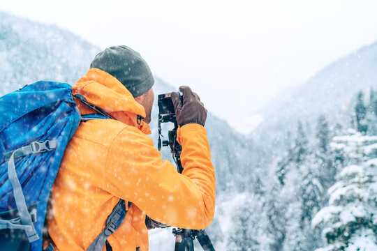 Photographer dressed orange softshell jacket with backpack making a landscape shoot using a digital camera and tripod while he trekking winter mountains route. Photographer occupation concept image.