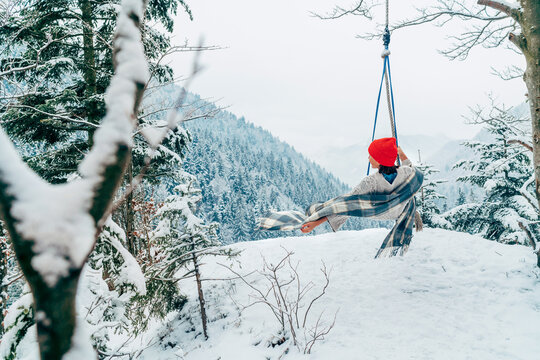 A young woman in warm clothes, checkered scarf and Red Cap swinging on a swing between forest trees with picturesque snowy mountain view. Wintertime vacation concept image.