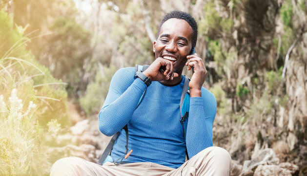 Young African ethnicity man talking via cellphone with somebody and cheerfully laughing as he having a hiking walk in the tropical forest. Happy people, network technology, or traveling concept.