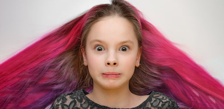 a child with colored hair and a surprised expression, red and purple hair spread out in different directions.