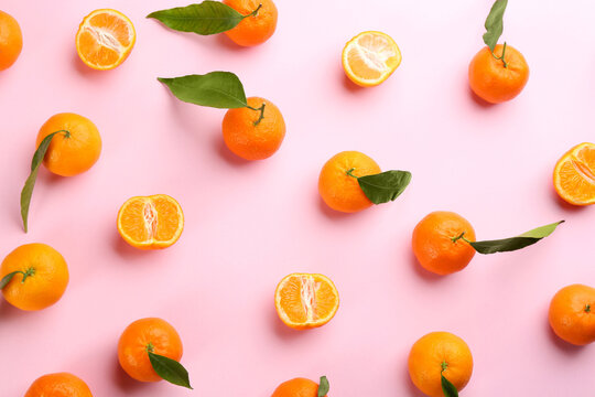 Fresh ripe tangerines with green leaves on pink background, flat lay