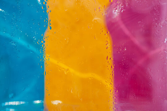 Abstract picturesque blurred tricolor with raindrops on glass, neon lights. Modern background