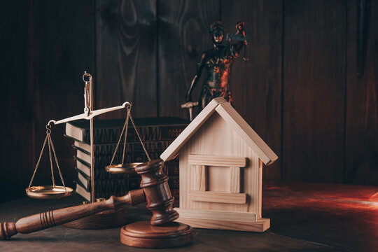 Judge gavel and wooden house model at courtroom. Estate law and property auction concept.