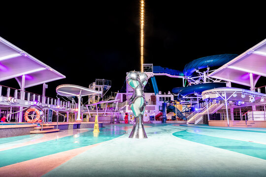 At Sea - October 11 2019: Empty open top deck onboard Norwegian (NCL) Cruise Ship  with metallic sculpture. No people on dance floor for night entertainment. Waterslide and clear sky in background.