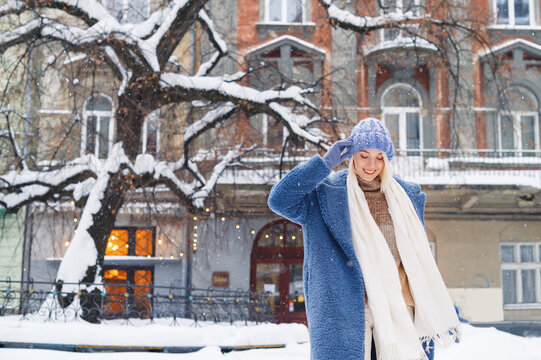 Happy smiling girl walking in street of European city. Model wearing blue faux fur coat, hat, white scarf. Winter, Christmas, New Year holidays, travel conception. Copy, empty space for text