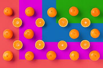 Fruit pattern of fresh orange tangerine or mandarin on colorful background. Flat lay, top view. Pop art design, creative summer concept. Citrus in minimal style.