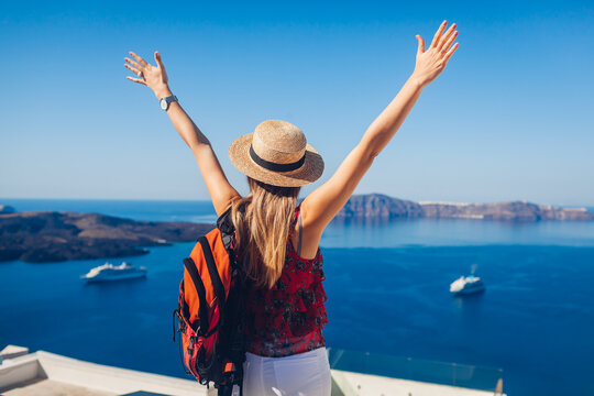 Happy woman traveler walking raising hands in Thera, Santorini island, Greece enjoying sea landscape. Summer vacation