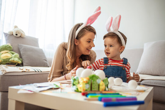 Having fun during Easter preparation. Portrait of pretty young mother hugging little boy while celebrating Easter at home, copy space. Mother and son painting easter eggs
