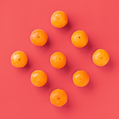 Fruit pattern of fresh orange tangerine or mandarin on living coral background. Flat lay, top view....