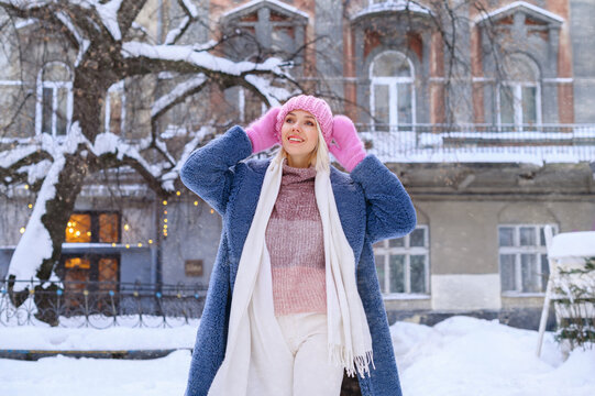 Winter, Christmas, New Year holidays, travel concept: happy smiling girl walking in street of European city. Model wearing blue faux fur coat, pink hat, gloves, white scarf. Copy, empty space for text