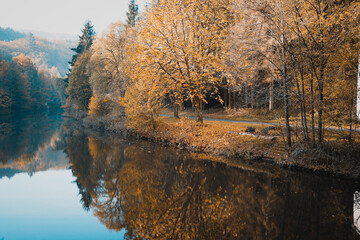 Tranquil view of a river with autumn trees reflected on the water near a pathway