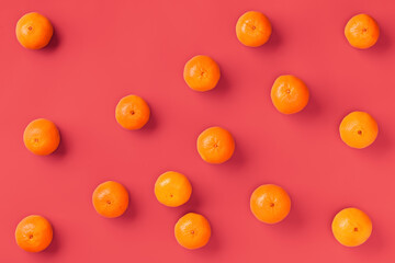 Fruit pattern of fresh orange tangerine or mandarin on living coral background. Flat lay, top view. Pop art design, creative summer concept. Citrus in minimal style.