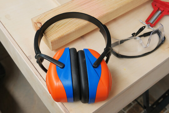A picture with noise effect of industrial sound proof ear and glass protector on the wood used during furniture making.