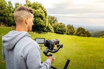 Fototapeta Young muscular Caucasian man manning a camera on top of a gimbal while working recording a scene in the middle of a field. Videomaker with steadicam and professional team working.