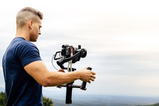 Young muscular Caucasian man manning a camera on top of a gimbal while working recording a scene in the middle of a field. Videomaker with steadicam and professional team working.