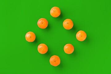 Fruit pattern of fresh orange tangerine or mandarin on green background. Flat lay, top view. Pop art design, creative summer concept. Citrus in minimal style.