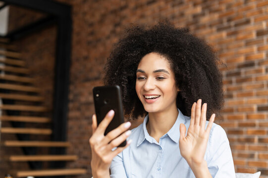 Young mixed-race African-American woman talking online on mobile phone, sitting in the chair against brick wall, video-calling with family coworkers, chatting, greeting friend with high five, waving