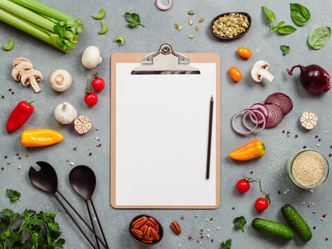 Food ingredients, salad serving utensils and clipboard with white paper sheet. Various of vegetarian cooking ingredients on gray background.Recipe book concept.Copy space for text.Top view or flat lay