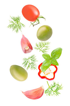Isolated vegetables. Mixed tomatoes, dill, green olives, basil, bell pepper and garlic falling down isolate on white with clipping path as package design element. Full depth of field.