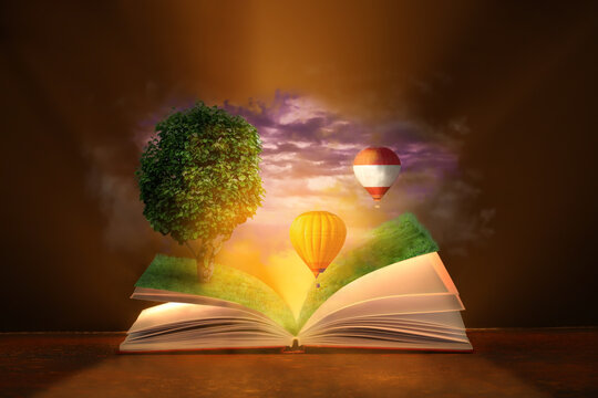 Open magic book with flying hot air balloons and growing tree on dark background