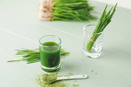 Glass with fresh wheatgrass juice and powder on color wooden background