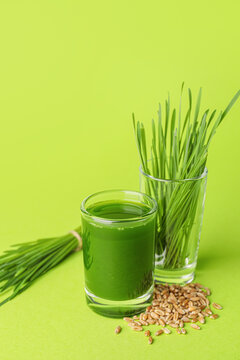 Glass with fresh wheatgrass juice and seeds on color background