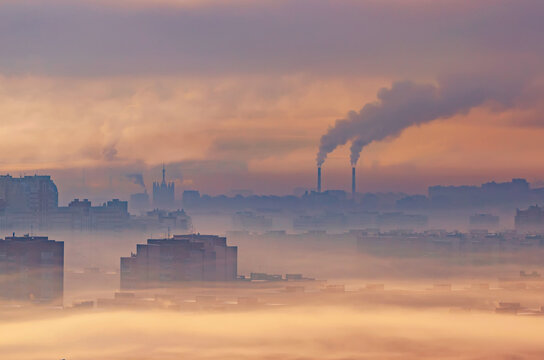 Urban industrial landscape, residential buildings buried in smoke and smog, chemical plants emit smoke into the atmosphere.