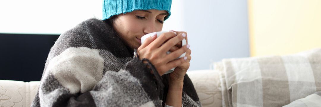 Sick woman in hat under blanket holds cup of medicine. Self isolation at home during coronavirus epidemic concept.