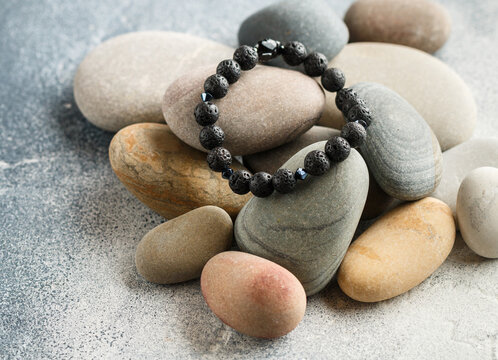 Beautiful bracelet made of natural black volcanic lava. Jewelry made of round-shaped beads is placed on large sea stones. Selective focus,  copy space