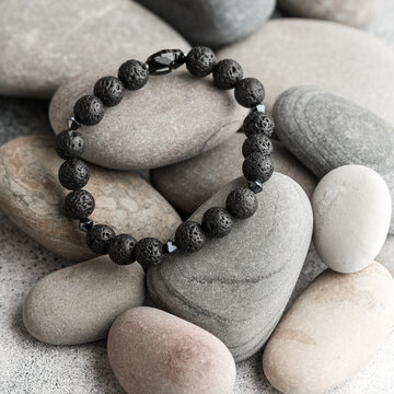 Beautiful bracelet made of natural black volcanic lava. Jewelry made of round-shaped beads is placed on large sea stones. Selective focus, square picture