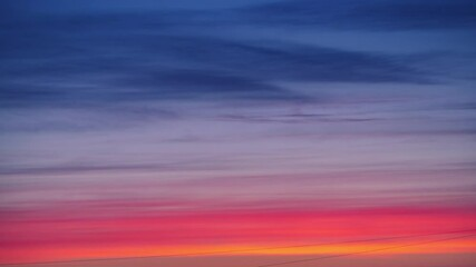 Fotobehang - Colorful red and blue clouds moving in epic sunset sky over city skyline. Abstract background, 4K UHD.