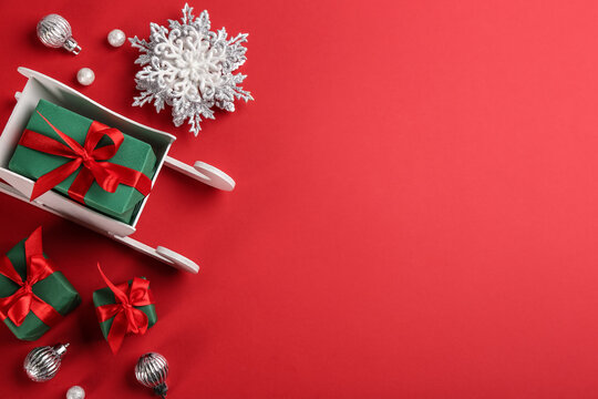 Beautiful Christmas composition with miniature sleigh on red background, flat lay. Space for text