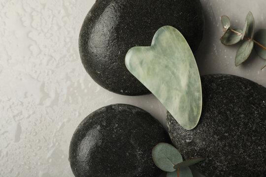 Jade gua sha tool, spa stones and eucalyptus branches on grey table, flat lay
